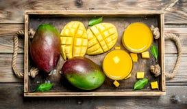 Mangofruktsaft i ett exponeringsglas på magasinet royaltyfria foton
