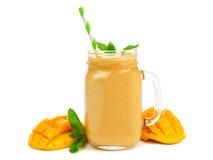 Mangokokosnoot smoothie in een glas van de metselaarkruik met munt en stro op wit wordt geïsoleerd dat Stock Afbeeldingen