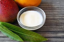 Mangokroppsmör i en glass bunke och den nya mogna organiska mango bär frukt och sidor på gammal träbakgrund Arkivbild