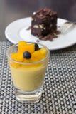 Mangopudding in einem Glas- und Schokoladenschokoladenkuchen als Hintergrund Lizenzfreie Stockbilder
