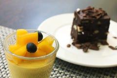 Mangopudding in einem Glas- und Schokoladenschokoladenkuchen als Hintergrund Lizenzfreies Stockfoto