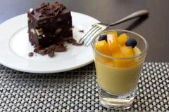 Mangopudding in einem Glas- und Schokoladenschokoladenkuchen als Hintergrund Stockfoto