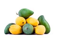 Mangos maduros de un amarillo de la pila y mangos verdes frescos en la comida sana de la fruta del fondo blanco aislada Imágenes de archivo libres de regalías