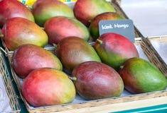 Mangos maduros en una caja en mercado Rebanadas anaranjadas de la piña y del kiwi foto de archivo libre de regalías