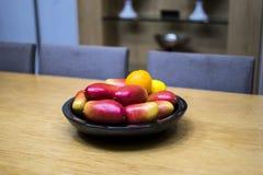 Mangos, naranjas, y limones de Apple en el cuenco en la cocina fotografía de archivo