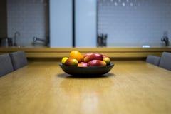 Mangos, naranjas, y limones de Apple en el cuenco en la cocina imágenes de archivo libres de regalías