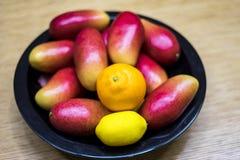 Mangos, naranjas, y limones de Apple en el cuenco en la cocina foto de archivo libre de regalías