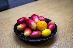 Mangos, naranjas, y limones de Apple en el cuenco en la cocina imagen de archivo libre de regalías