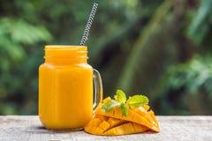 Mangosmoothie i en glass murarekrus och mango på en grön backgro Royaltyfria Bilder