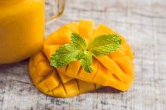 Mangosmoothie i en glass murarekrus och mango på en grön backgro Arkivbild