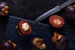 Mangostan i przekrój poprzeczny pokazuje gęstego purpurowego ciało królowa owoc skóry i białego, Wyśmienicie mangostan owoc obraz royalty free