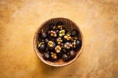 Mangostanes frescos en la cesta de bambú Imagen de archivo libre de regalías