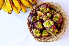 Mangostanfrucht im traditionellen Korb und Bananen werden lokalisierten im Spitzenwinkel gefangen genommen lizenzfreie stockfotografie