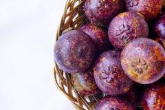 Mangostanfrucht im traditionellen Korb werden lokalisierte im Spitzenwinkel gefangen genommen stockbild