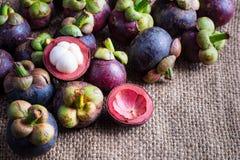 Mangostanfrucht und Querschnitt, welche die starke purpurrote Haut und das w zeigen Lizenzfreies Stockfoto