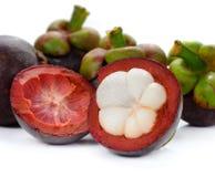 Mangostanfrucht und Querschnitt, welche die starke purpurrote Haut und das w zeigen lizenzfreie stockfotos
