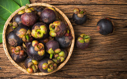 Mangosteen in basket on wood background Stock Photo