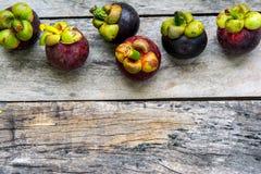 Mangosteen på wood bakgrund som är färgrik av frukt Royaltyfri Bild