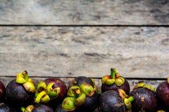 Mangosteen på wood bakgrund som är färgrik av frukt Fotografering för Bildbyråer