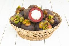 Mangoteen e mangoteen a fatia na cesta no fundo branco de madeira A vista superior e zumbe dentro Fotografia de Stock Royalty Free