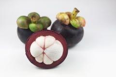 Mangoustans d'isolement Deux fruits et un demi- entiers d'isolement dessus Photo libre de droits