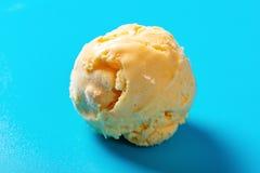Mangowa smaku lody piłka na błękitnym tle obrazy stock