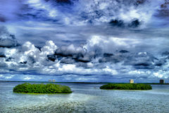 Mangrove islands under clouds. Two tropical islands under a big sky filled with clouds Stock Image