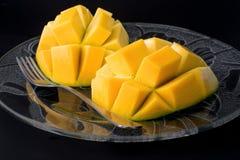 Mangue coupée en tranches sur le fond noir Images libres de droits
