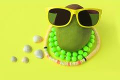 Mangue verte et rouge juteuse mûre dans les lunettes de soleil et les perles sur le fond jaune en pastel Copiez l'espace Style de images libres de droits