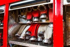 Mangueiras de fogo roladas, arranjadas nas fileiras, no compartimento de luva do carro de bombeiros fotografia de stock