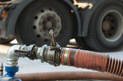 Mangueiras do caminhão para a estação e as bombas do combustível Imagem de Stock