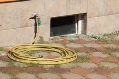 Manguera de jardín que pone en el pavimento con la mala hierba y con el viento viejo sucio Imagen de archivo libre de regalías