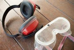 Manguitos del oído y vidrios de la protección ocular en fondo de la madera Foto de archivo libre de regalías