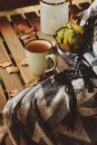 Manhã acolhedor do outono na casa de campo, no copo do chá e na cobertura morna na tabela de madeira Fotografia de Stock