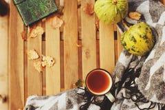 Manhã acolhedor do outono na casa de campo, no copo do chá e na cobertura morna na tabela de madeira Imagem de Stock