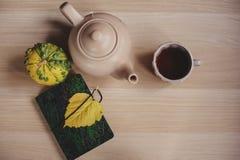 Manhã acolhedor do outono na casa de campo, no copo do chá e na cobertura morna na tabela de madeira Imagens de Stock Royalty Free