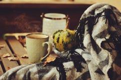 Manhã acolhedor do outono na casa de campo, no copo do chá e na cobertura morna na tabela de madeira Fotos de Stock