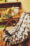 Manhã acolhedor do outono na casa de campo, no copo do chá e na cobertura morna na tabela de madeira Fotos de Stock Royalty Free