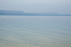 Manhã azul enevoada com penhascos e água clara fotos de stock royalty free