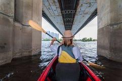 Manhã da reunião em caiaque Vista traseira de bu kayaking da moça o rio e sob a ponte Conceito urbano da exploração fotografia de stock