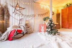 Manhã de Natal Cadeira de balanço com as decorações pela lenha e pela parede de madeira imagem de stock royalty free