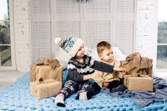 Manhã de Natal do tema O menino de duas crianças e o irmão e a irmã caucasianos da menina estão sentando-se na cama em um abraço  fotos de stock