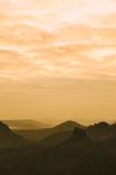 Manhã enevoada alaranjada, vista sobre a rocha ao vale profundo completamente da paisagem sonhadora da mola da névoa clara dentro Imagem de Stock Royalty Free