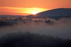 Manhã enevoada da área montanhosa com raia de luz. Fotografia de Stock