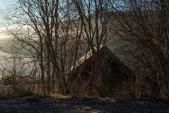 Manhã enevoada e atmosférica com nascer do sol sobre o lago, a montanha e uma casa de campo pequena místico na região selvagem co foto de stock