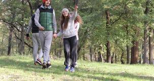 Manhã exterior de passeio Autumn Park de Forest Two Couple Holding Hands do grupo dos jovens filme