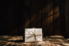 Manhã festiva, um raio de luz do sol através da janela cai em uma caixa com um presente foto de stock royalty free