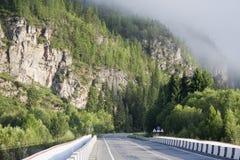 Manhã na estrada da montanha. Imagens de Stock