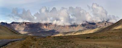 Manhã na estrada de Leh-Manal: a estrada asfaltada passa com o deserto alto, no fundo as montanhas, o alvorecer ensolarado e o po Fotografia de Stock Royalty Free