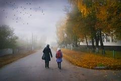 A manhã nevoenta do outono, ao longo da estrada lá é dois - uma mulher e fotos de stock